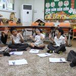 亚太国际学校的学生坐在地板上玩游戏