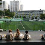 亚太国际学校的学生坐成一排,面对运动场