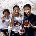庆南国际外国学校的学生在樱花树前
