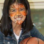 庆南国际外国学校的画着脸上彩绘的学生抱着篮球