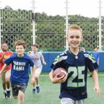韩国国际学校板桥校区的学生抱着橄榄球奔跑
