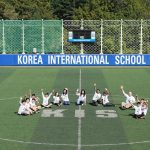 韩国国际学校板桥校区的学生坐在运动场上