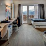 博苏蕾高山学院宿舍里的豪华寝室,有两个床和一个很长的书桌