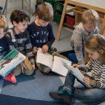 伯尔尼英国学校的5个小朋友做地毯上看图画书