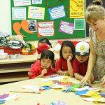 胡志明市英国越南国际学校的老师在教室里和学生一起做手工