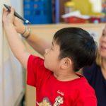 胡志明市英国越南国际学校的老师指导学生在白板上写字
