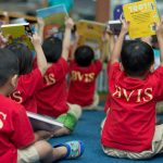 胡志明市英国越南国际学校的学生举起手中的故事书