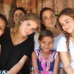 开罗美国学校的学生们和一个小女孩子在一起