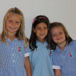 瑞士KSI国际学校的三个小学生穿着校服,开心地看着镜头