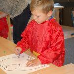 瑞士KSI国际学校的学生穿着红色的罩衫,在画画
