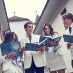 萝实学院的4个高中生,穿着西装,看着学校的年鉴,开心地笑