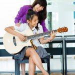 奥林匹亚学校的老师教学生弹吉他