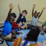 班珠尔美国国际学校的小朋友坐在地板上举起双手