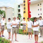 华中国际学校的学生在学校立柱前合影
