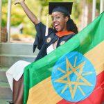 亚的斯亚贝巴国际社区学校的女学生穿着毕业服在旗帜后面挥手